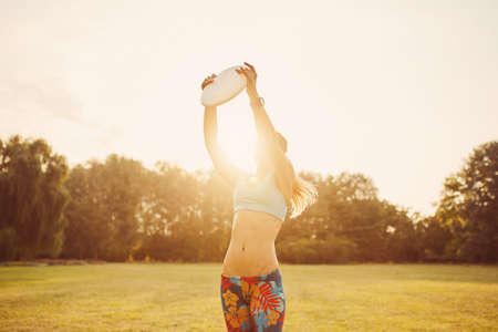 Young athletic girl playing with flying disc in the park. Professional player. Sport concept Stock Photo