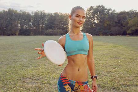 coordinacion: chica atlética joven que juega con el disco volador en el parque. Jugador profesional. Concepto de deporte. Último