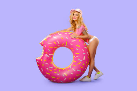 Beautiful sexy tattooed girl in studio isolated with the inflatable big donut. Dressed in a swimsuit with embroidered cakes Stock fotó