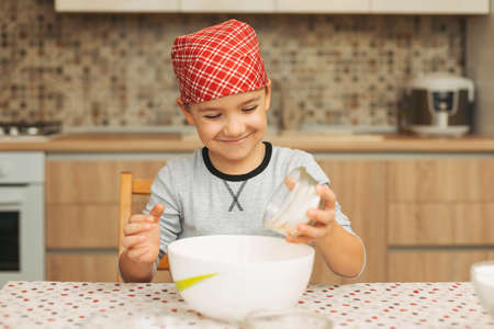 A seven years old boy is cooking in a luminous kitchen adding ingredients. Smiling boy pouring sugar into the bowl to cook biscuits, a cake at home. Stock Photo