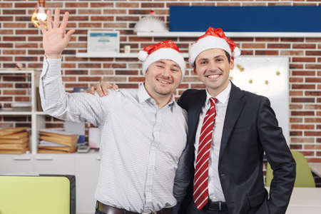 Portrait of two smiling corporate workers, director and his employee posing in Christmas time on the office background