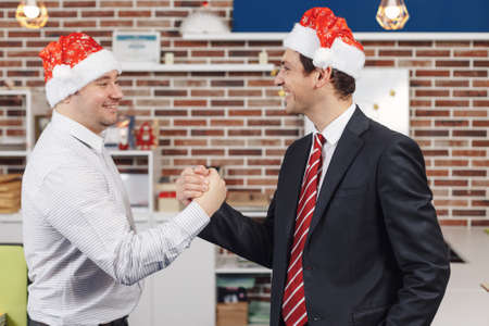 Two colleagues are happy to achieve maximum results for this year and to celebrate Christmas shaking hands. Team concept Stock Photo