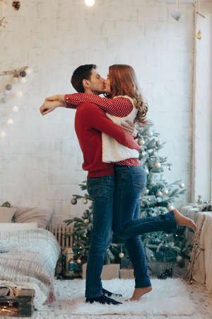 Picture showing young couple hugging and kissing over Christmas tree, full length