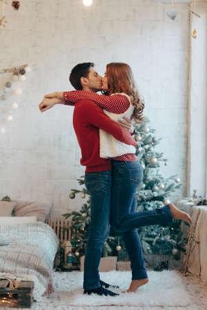Photo d'un jeune couple embrassant un arbre de Noël sur toute sa longueur
