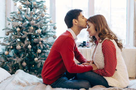 Happy loving couple enjoying Christmas. Young man kissing his girlfriend on forehead touching her hands sitting on a bed with decorated tree and window on background Stockfoto