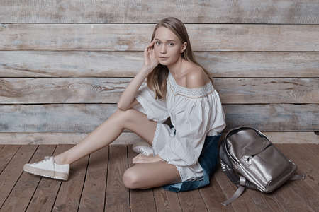 Beautiful girl wearing natural makeup, linen dress and boots. Concept of purity, youth, beautiful skin sitting on pastel wood background, with a silver backpack, touching face while looking to camera. Stock Photo