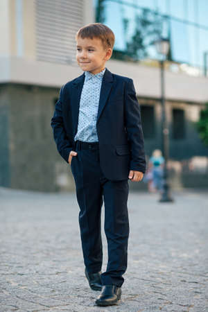 Concept future businessman. Boy in classic modern dark blue business costume and baby blue shirt walk on pedestrian street near building with hands in pockets thinking of future plans.