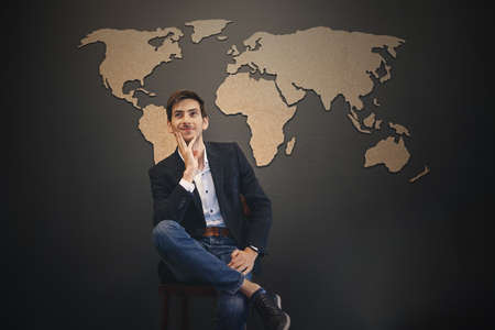 Dreaming big concept. Young man making plans and visualizing the future results in his imagination having an abstract world map on a gray wall on background. Dreams to travel all over the world. Stock Photo