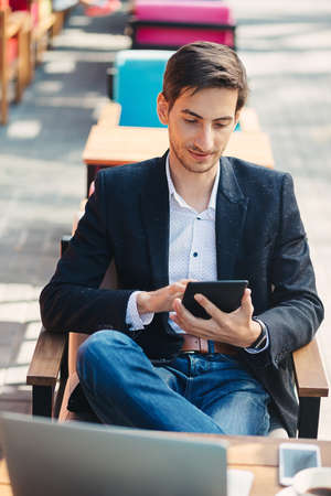 Young man employer reading resumes on portable touch pad before interview with specialists. Successful business worker is reading news on web via digital tablet, sitting on chair with leg over leg. Stock Photo