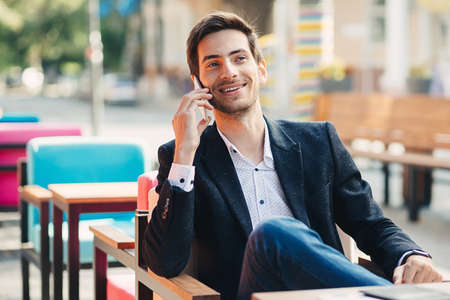 Portrait of handsome young smiling businessman dressed in casual jacket and shirt, on a stylish modern cafe terrace in the street, talking on the phone while sitting leg over leg. Stock Photo