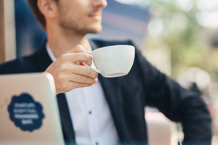Close-up hand of young businessman with handsome masculine chin in formal wear holding cup, mug of coffee