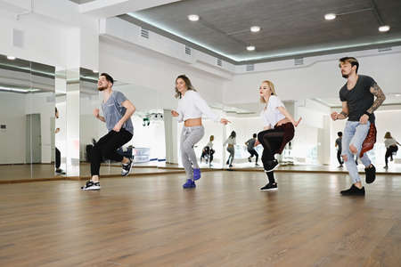 Group of four young hip-hop dancers, boys and girls, dancing in a studio. Beautiful active people repeating a performance.