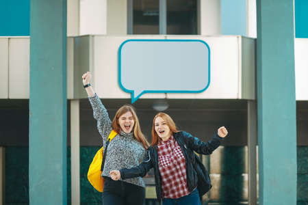 Advertising concept. Background with teenage girls students with backpacks, holding hands up shouting cheerfully. Text box frame above.