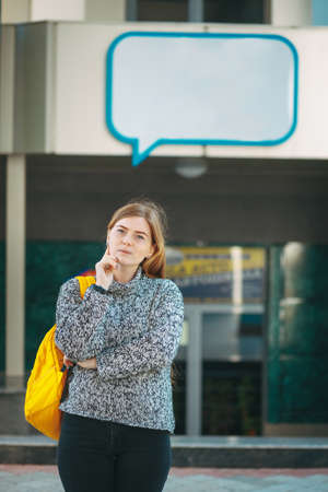 Advertising concept. Student girl thinking while touching her cheek with one finger and looking to camera. Text box frame above.