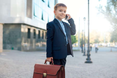 Concept future businessman. High angle of smiling businessman in formal wear standing on pedestrian street carrying a briefcase talking on the phone, urban gray pavage stone background.
