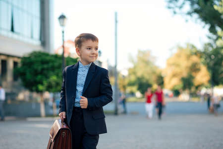 Portrait of future smiling businessman in formal wear walking around the street carrying a briefcase and holding jacket with arm, urban background.
