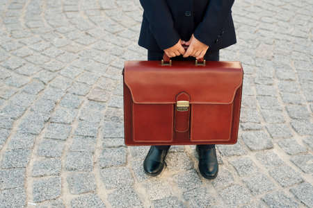 Future businessman holding, close up, leather briefcase while staying on street outdoor in city. leather bag with golden belt on gray stone background. Copy space available.