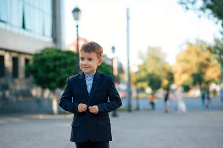Portrait, boy in classic dark blue business costume and baby blue shirt stand on pedestrian street near building and trees, close the jacket button. Banque d'images