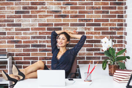Portrait of a relaxed smiling business woman sitting in a modern office with her legs on the table wearing high heels shoes and blouse with dots, holding hands on the head while looking to the camera.