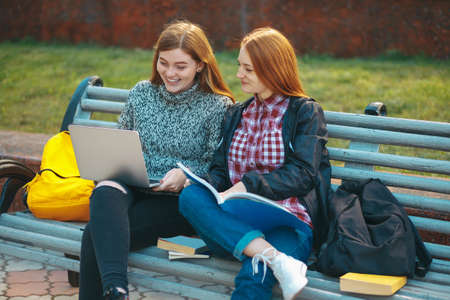 Attractive Young Adult Female Students on Bench Outdoors with Books and Laptop. College girls relaxing after study looking to computer sitting on bench outside campus autumn. 写真素材