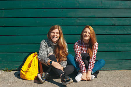 Natural reddish hipster girls having fun on a green wooden background. Cheerful friends spending time together. Laughing girls with backpacks relaxing in an autumn sunny day.