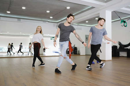 Group of three young hip-hop dancers, boys and girl, dancing in a studio. Beautiful active people repeating a performance.