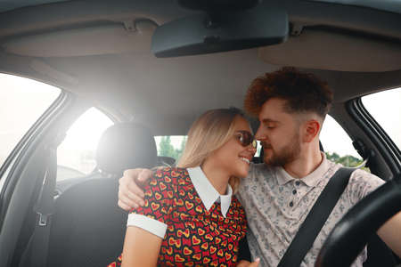 Young attractive man hugging his woman with affection while driving the car Stock Photo