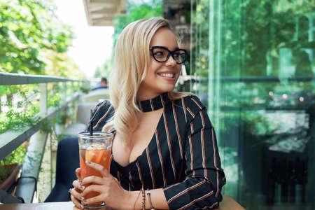 Eyewear model. Gorgeous blond fashion woman with wavy hair, white shiny teeth, wearing trendy transparent glasses while resting on cafe terrace with a fresh drink. Cool, trendy eyewear portrait.
