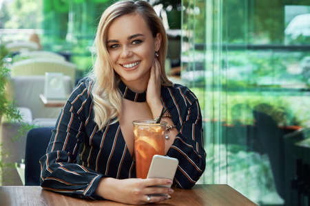 Portrait gorgeous woman holding phone in hand while sitting on the cafe terrace with a fresh drink with ice and orange slices, posing with a shiny white smile, looking to camera, touching the neck.