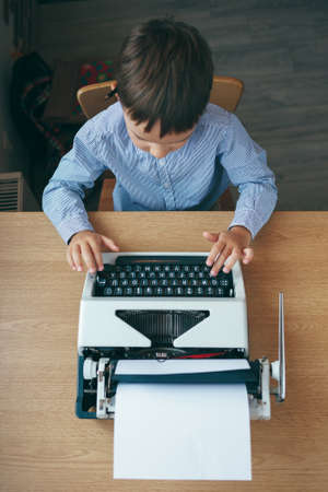 Top view, preschool journalist boy sitting at table and typing typewriter with a pencil on the top of year. Businessman using typewriter at desk in office. Business and new technology.