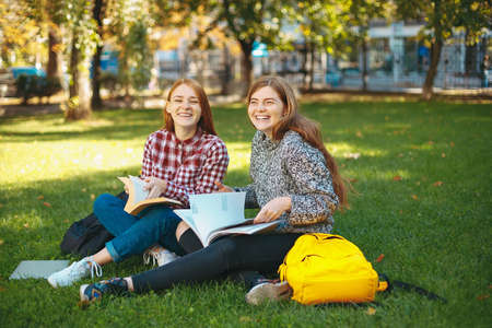 Attractive smiling students having fun outdoors on campus at the university. Beautiful college girls with reddish hair sit on the campus sod grass with crossed legs and books.