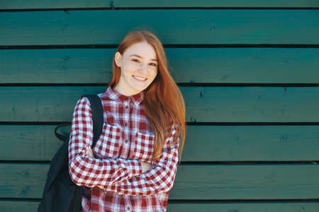 Handsome student with backpack standing outside on green wooden background. Portrait of reddish high school girl dressed in plaid shirt smiling holding crossed hands, copy space available. 免版税图像