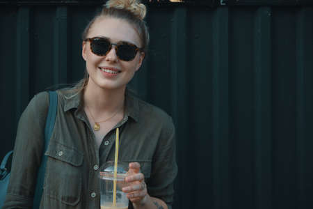 Progressive modern woman, wearing sunglasses, backpack and stylish romper, posing on a dark gray metallic background with copy space while drinking confident a glass of refreshing cold drink.