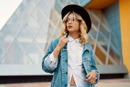 Close-up portrait of a cheerful white woman in glasses touching her jacket collar on urban background. Photo of fashionable girl with beautiful blonde hair posing for the camera.