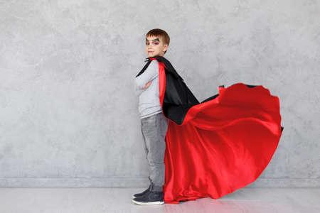 Retrato de perfil de niño con maquillaje de vampiro de Halloween y agitando su capa roja y negra, sobre un fondo de textura gris Niño lindo con traje de superhéroe con las manos cruzadas, espacio de copia disponible.