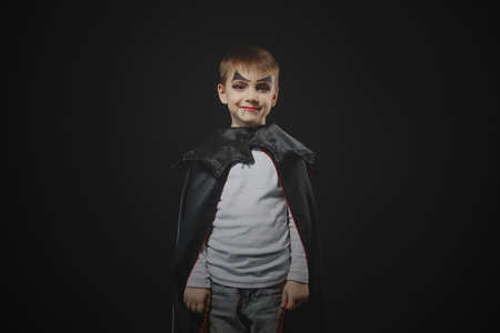 Cute boy dressed up as vampire, dracula for halloween party wearing a black cloak and casual jeans is smiling while looking at camera on black studio background with self made white balloons ghosts. 版權商用圖片