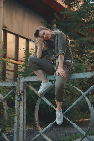 Stylish girl posing in the street sitting on a steel fence with bent legs. Urban style. Street fashion.