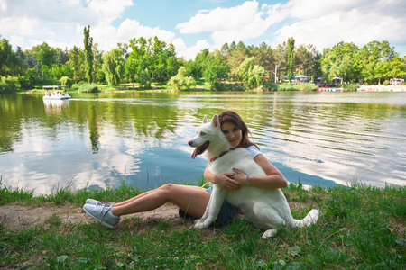 Love between people and animals concept. Woman hugging her pet dog, with closed eyes, smiling with affection sitting on the grass with amazing landscape in background, water reflection trees and sky.