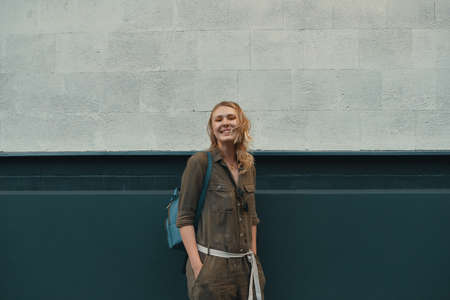 A hipster girl with long blonde hair, wearing a stylish romper and a backpack is looking aside while standing on a wall background on a street. Horizontal mock up. Empty space for text or design. Imagens