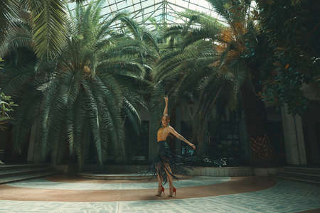 Dancing is a lifestyle concept. Young beautiful woman dancers performing in an amazing tropical garden with palm trees in the background under a glass rooftop. Passion, motivation and inspiration.