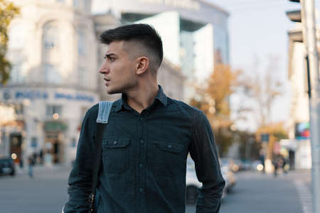 Young modern man walking European city. A man traveler with his backpack exploring city