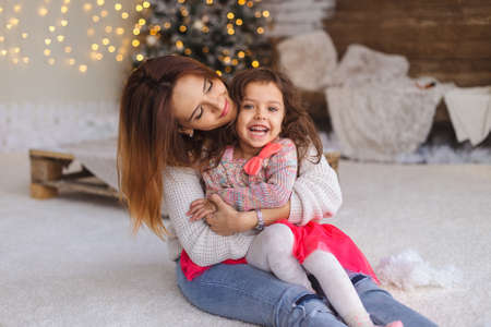 Happy loving family. Mother and her daughter girl play at home in Christmas lights. Funny mom and lovely child having fun indoors.