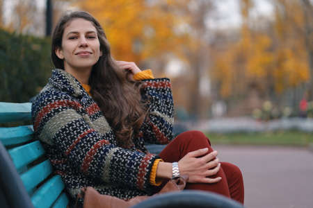 Pretty young woman in good mood posing in the autumn day, while sitting on a bench, enjoying the good weather. Stock Photo