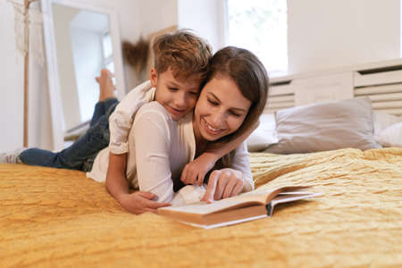 Mother and son reading a book while lying on the bed at home Banco de Imagens