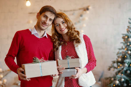Happy young couple with Christmas presents looking at camera, to each other on a decorated tree background