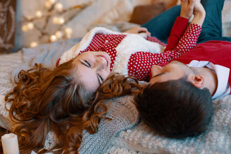 Young couple laying on the bed smiling with heads upside down. Young attractive couple lays on the bed, looking to each other spending time together. Top view Banco de Imagens