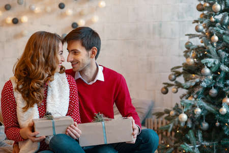 Happy young couple with Christmas presents looking to each other on a decorated tree background