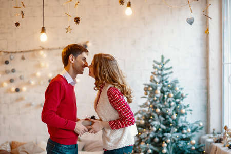 Young couple kissing while holding together a present box, with Christmas decorations in background