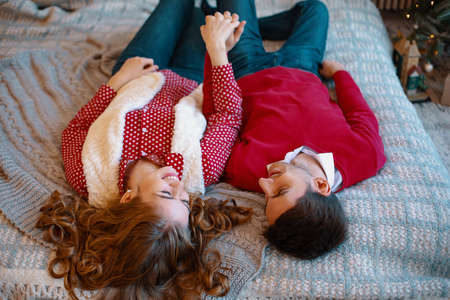 Young attractive couple lays on the bed, looking to each other spending time together. Top view. Young couple laying on the bed smiling with heads upside down. Imagens