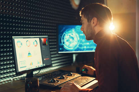 Confident Man Video Editor Works with Footage in Creative Office Studio. Banco de Imagens